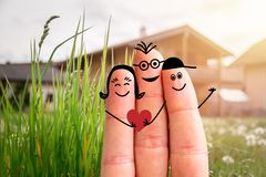 Family moving into a new home concept: Painted finger family in front of a blurry house