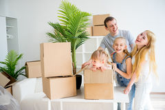 Family moving into new home. Moving into new home. Happy family with cardboard boxes Stock Photography