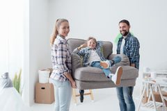 Family moving into a new home. Happy young family moving into a new home, a men and a women are carrying a new armchair and their son is sitting on it Royalty Free Stock Photos