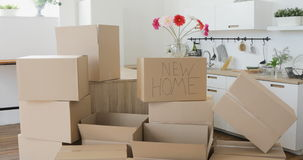 Family Moving Into New Home. Moving to a new home concept. New home owners unpacking boxes, footage of big cardboard boxes in new home stock video footage
