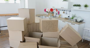 Family moving into new home. Moving to a new home concept. New home owners unpacking boxes, footage of big cardboard boxes in new home stock video