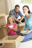 Family Moving Into New Home Surrounded By Packing Boxes Stock Photography