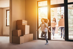 Family moving in new house. Happy family with cardboard boxes in new house at moving day royalty free stock image