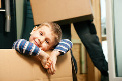 Family moving in their new house. Family moving in their new home. The son is sitting inside a moving box. In the background the father - or a mover (only legs Stock Photography