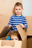 Family moving in their new house. Family moving in their new home. The sons are playing with a moving box stock images