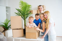 Family moving to a new home. Moving to a new home. Happy family with cardboard boxes Stock Photo