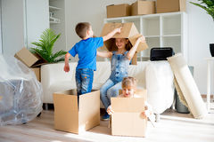 Family moving to a new home. Moving to a new home. Happy family with cardboard boxes Stock Photos