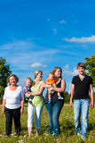 Family and multi-generation - fun on meadow. Family and multi-generation - mother, father, children and grandmother having fun on meadow in summer Royalty Free Stock Photography