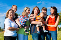 Family and multi-generation - fun on meadow. Family and multi-generation - mother, father, children and grandmother having fun on meadow in summer Stock Photo