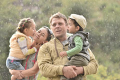 Family in nature on a rainy day with children Royalty Free Stock Photos