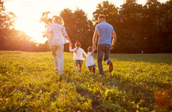 Family in nature together, back view. Family running together Family in nature, back view royalty free stock images