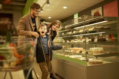 Family near display with cakes Stock Image