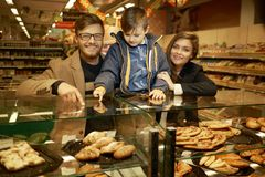 Family near display with cakes Royalty Free Stock Photo