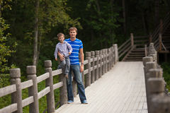 Father and son near fence in park Royalty Free Stock Images