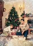 Family near fireplace in Christmas decorated house Stock Photography