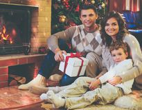 Family near fireplace in decorated house interior. Family near fireplace in Christmas decorated house interior with gift box Stock Image