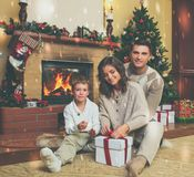Family near fireplace in decorated house interior. Family near fireplace in Christmas decorated house interior with gift box Royalty Free Stock Images