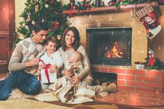Family near fireplace in decorated house interior. Family near fireplace in Christmas decorated house interior with gift box Royalty Free Stock Photos