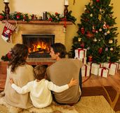 Family near fireplace in Christmas house Stock Image