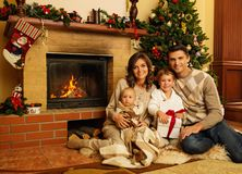Family near fireplace in Christmas house. Family near fireplace in Christmas decorated house interior with gift box royalty free stock image
