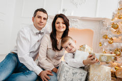 Family near the fireplace with Christmas presents Royalty Free Stock Photo