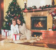 Family near fireplace in decorated house interior. Family near fireplace in Christmas decorated house interior with gift box Stock Photo