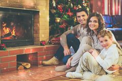 Family near fireplace in decorated house interior. Family near fireplace in Christmas decorated house interior with gift box Royalty Free Stock Photography