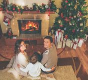 Family near fireplace in decorated house interior. Family near fireplace in Christmas decorated house interior with gift box Royalty Free Stock Image