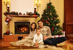Family near fireplace in house interior Royalty Free Stock Photo