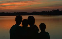 Family near the river against the sunset Stock Images