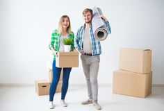 Family, new apartment and relocation concept - Young couple moving in new house.  royalty free stock photography