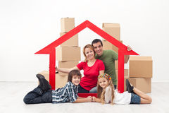 Family in a new home concept. Happy family in a new home concept - sitting with cardboard boxes royalty free stock images