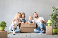 Family New Home Moving Day House Concept. Happy family with two kids playing into new home. Father, mother and children having fun together. Moving house day and stock images
