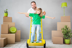 Family New Home Moving Day House Concept. Happy family playing into new home. Father and child having fun together. Moving house day and express delivery concept stock photo
