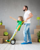 Family New Home Moving Day House Concept. Happy family playing into new home. Father and child having fun together. Moving house day and express delivery concept Royalty Free Stock Photos