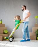 Family New Home Moving Day House Concept. Happy family playing into new home. Father and child having fun together. Moving house day and express delivery concept Stock Images