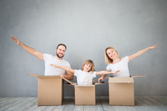 Family New Home Moving Day House Concept. Happy family playing into new home. Father, mother and child having fun together. Moving house day and express delivery Royalty Free Stock Photography