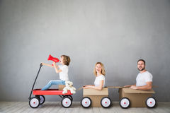 Family New Home Moving Day House Concept. Happy family playing into new home. Father, mother and child having fun together. Moving house day and express delivery Royalty Free Stock Image