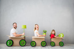 Family New Home Moving Day House Concept. Happy family playing into new home. Father, mother and child having fun together. Moving house day and express delivery stock image
