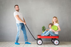 Family New Home Moving Day House Concept. Happy family playing into new home. Father, mother and child having fun together. Moving house day and express delivery stock images