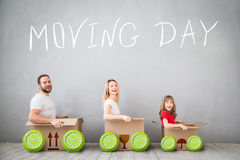 Family New Home Moving Day House Concept. Happy family playing into new home. Father, mother and child having fun together. Moving house day and express delivery stock photo