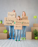 Family New Home Moving Day House Concept. Happy family playing into new home. Father, mother and child having fun together. Moving house day and real estate Royalty Free Stock Images