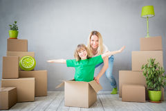 Family New Home Moving Day House Concept. Happy family playing into new home. Mother and child having fun together. Moving house day and express delivery concept Royalty Free Stock Photo