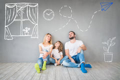 Family New Home Moving Day House Concept. Happy family sitting on wooden floor. Father, mother and child having fun together. Moving house day, new home and royalty free stock photography