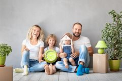 Family New Home Moving Day House Concept. Happy family with two kids playing into new home. Father, mother and children having fun together. Moving house day and stock photography