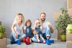 Family New Home Moving Day House Concept. Happy family with two kids playing into new home. Father, mother and children having fun together. Moving house day and stock photos