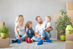Family New Home Moving Day House Concept. Happy family with two kids playing into new home. Father, mother and children having fun together. Moving house day and royalty free stock images