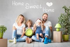 Family New Home Moving Day House Concept. Happy family with two kids playing into new home. Father, mother and children having fun together. Moving house day and royalty free stock photo