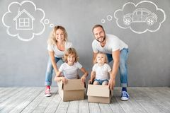 Family New Home Moving Day House Concept. Happy family with two kids playing into new home. Father, mother and children having fun together. Moving house day and royalty free stock photography