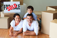 Family in new house lying on floor with boxes Stock Photo